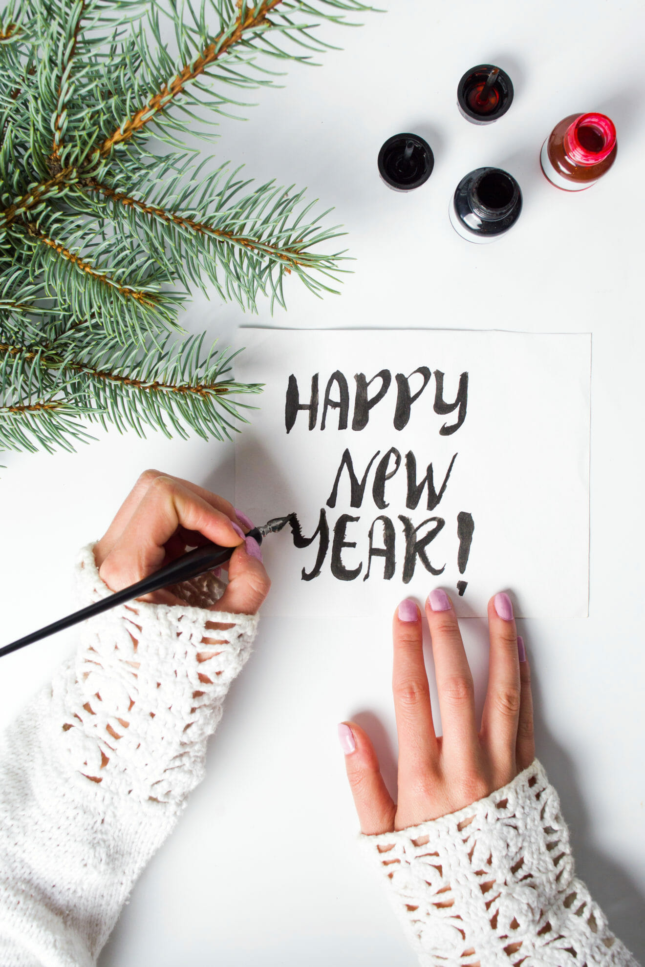 Girl writing Happy new year calligraphy card